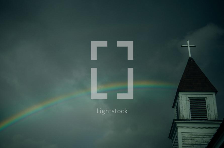 a rainbow in a gray sky and a church steeple