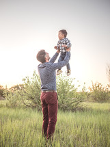 father holding up a toddler boy