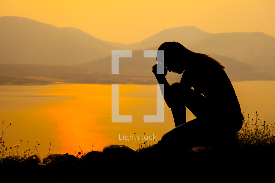 a silhouette of a woman kneeling in prayer by a lake