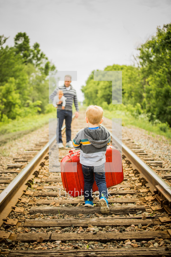 A little boy carries a red suitcase down a railroad track toward his father and sibling.