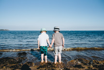 brothers holding hands standing on a rocky beach