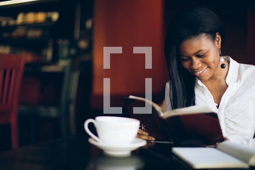 woman reading from a journal at a coffee house during a Bible study