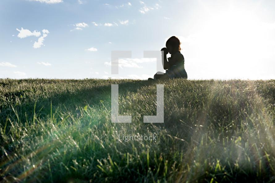 a child sitting in grass praying