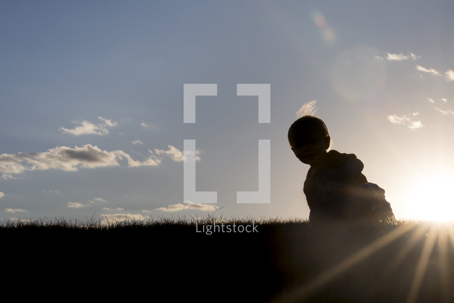 silhouette of a toddler in the grass