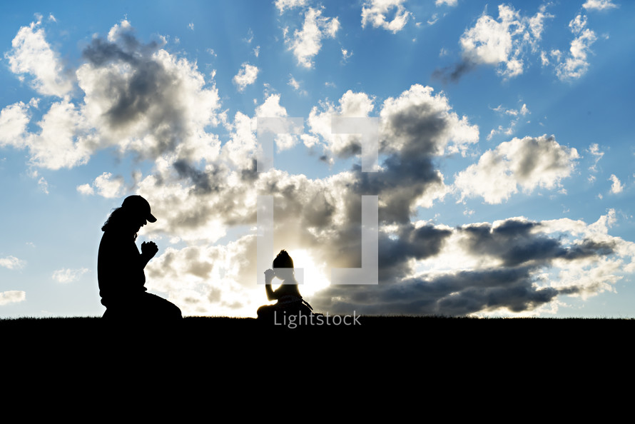 mother and daughter kneeling in prayer