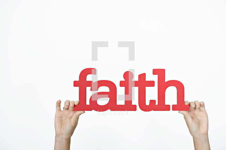 word faith in red held up by hands