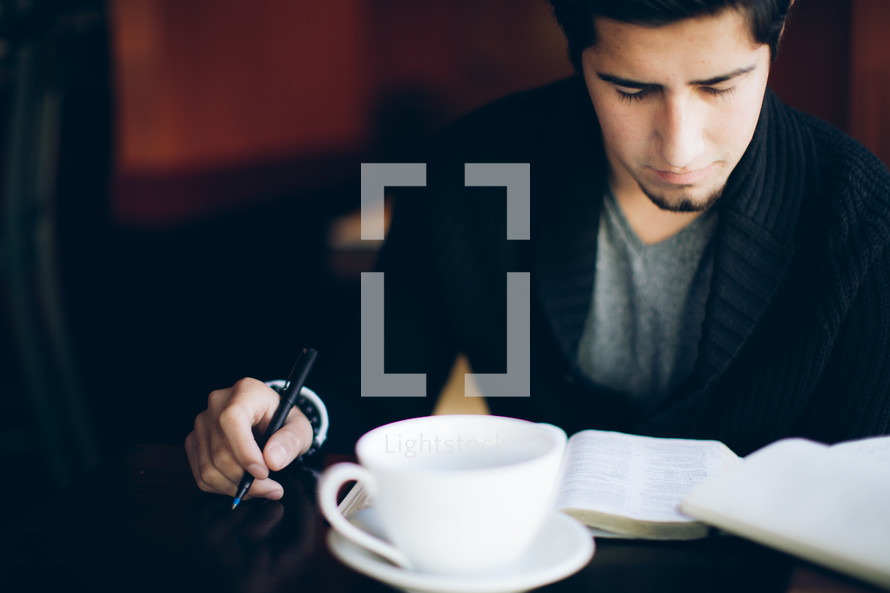 man reading a Bible and holding a pen sitting in a coffee house