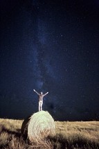 a man with raised hands standing on a hay bale under stars in the night sky
