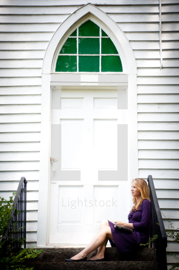 woman sitting on the steps in front of a church