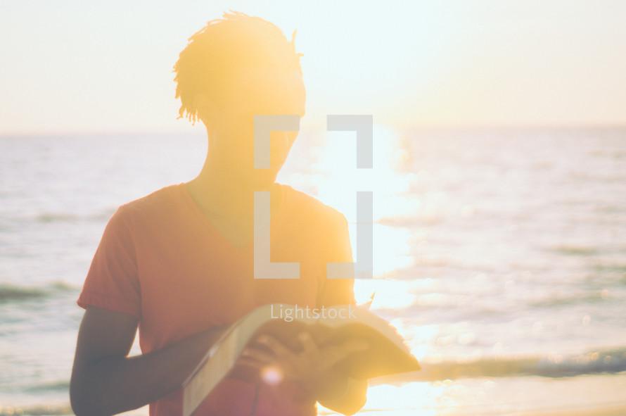 man standing on a beach reading a Bible