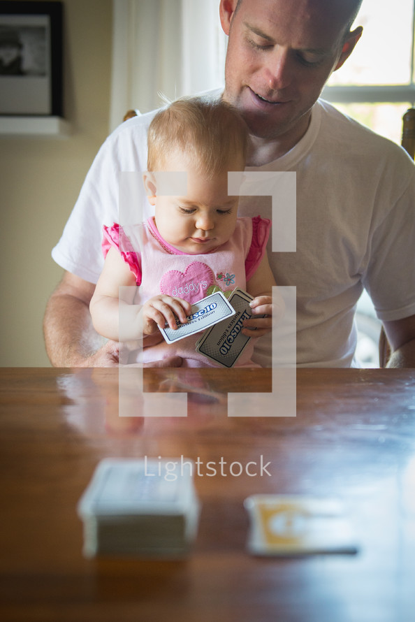 A baby girl with playing cards sitting in her father's lap.