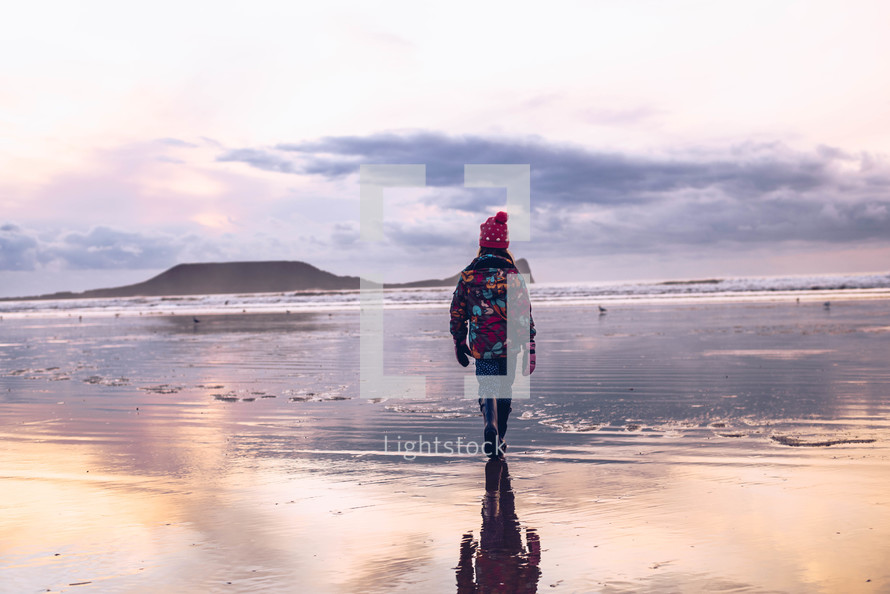 a girl walking on a wet sand on a beach in winter