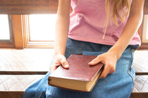 girl praying with a Bible in her lap