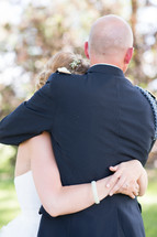 Embrace between a father and daughter on her wedding day.