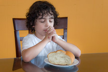 a child praying over bread