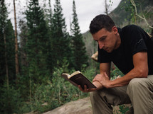 man reading a Bible outdoors