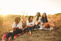 friends sitting on a hill at sunset