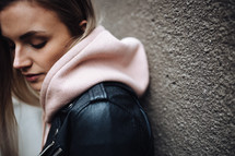 a woman in a leather jacket and pink hoodie
