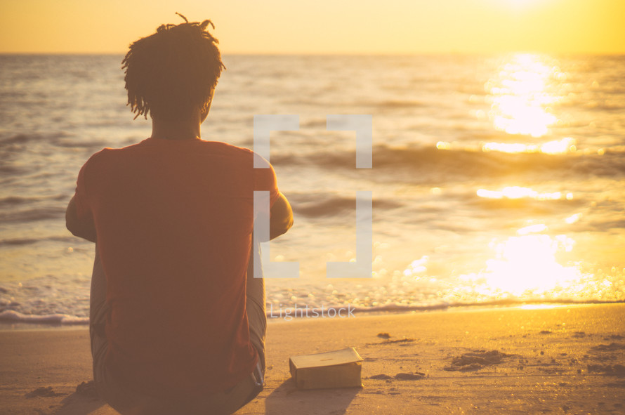 African-American man sitting on a beach with a Bible at sunrise