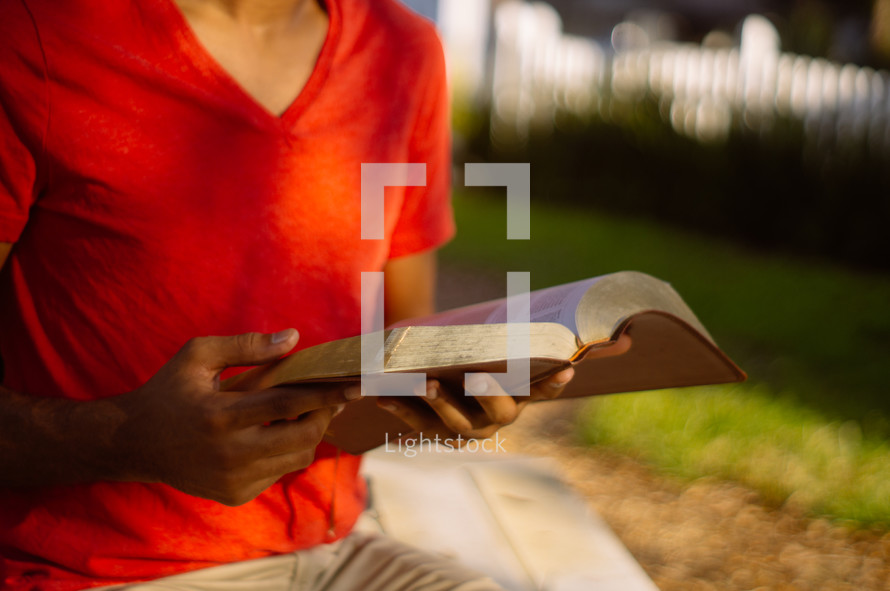 torso of a man reading a Bible outdoors
