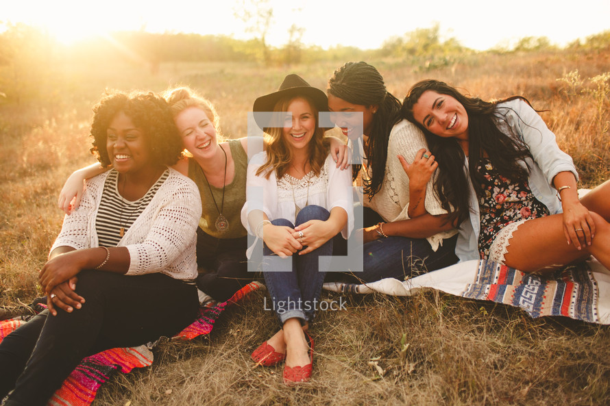 portrait of friends sitting on blankets in the grass