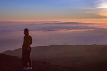 a woman standing on a mountaintop above the clouds looking out