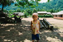 a toddler boy standing barefoot in the dirt