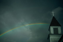 a rainbow in a gray sky and a church steeple