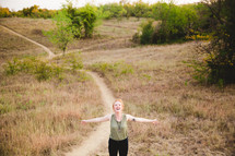 woman standing on a path with open arms