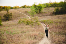 woman walking up hill on a trail