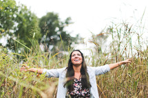 woman with open arms standing outdoors in tall grass