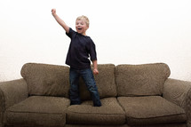 Boy standing on couch with hand raised in excitement with white background.