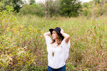 woman in a black hat standing in tall grasses