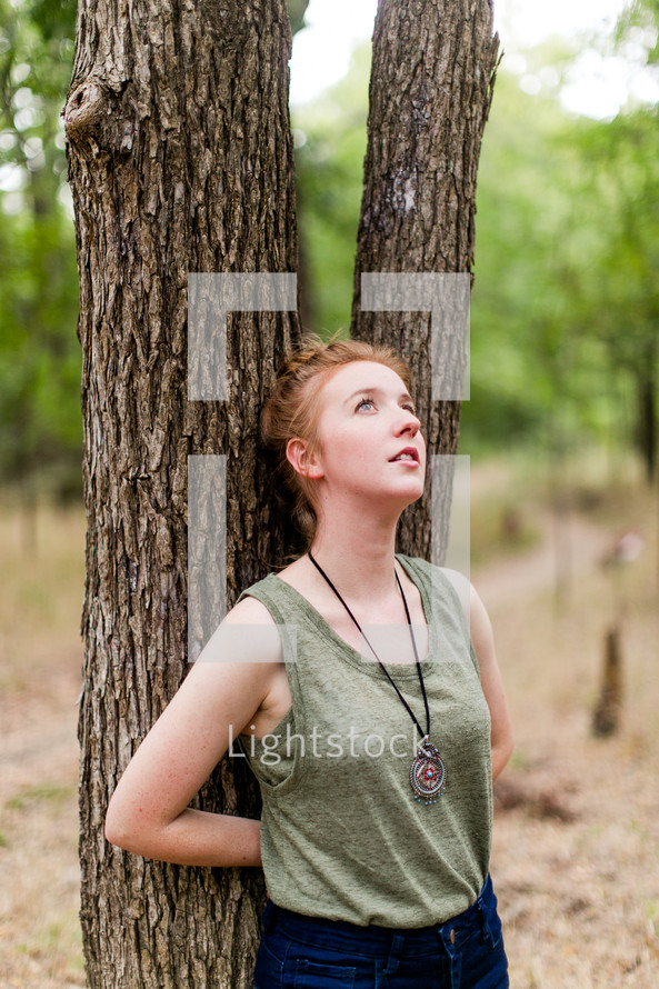 woman leaning on a tree looking up