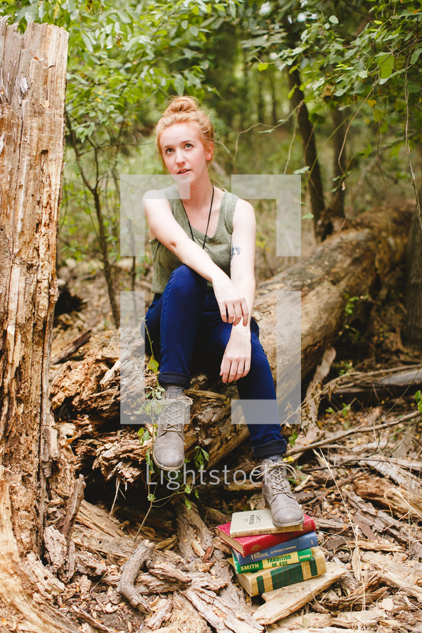 woman sitting on a log with her foot on a stack of books