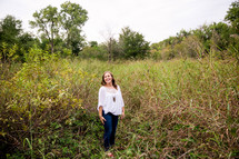 portrait of a young woman standing outdoors in tall grasses