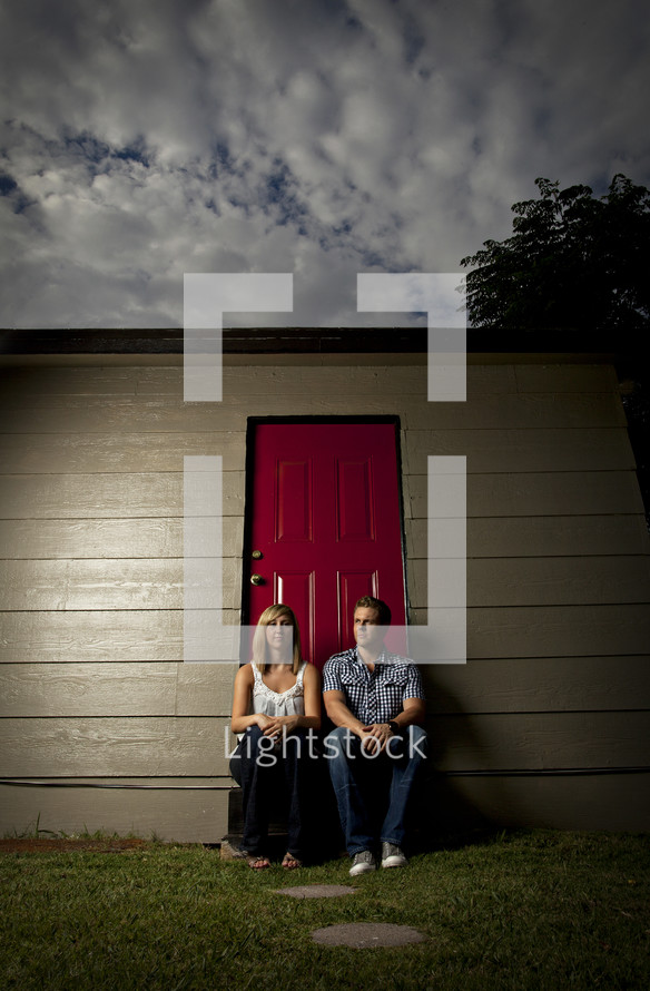 Couple sitting in front of door