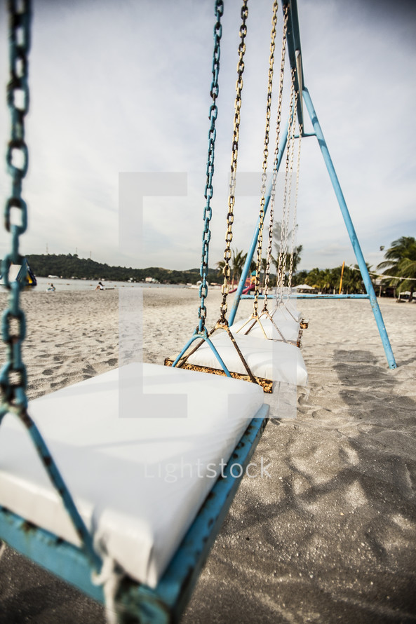 A swing set at a playground on the beach.