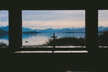 A cross on a windowsill looking out on a lake and mountain range.