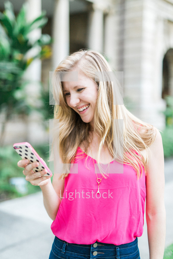 smiling woman looking at her cellphone screen