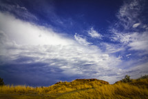 grassy, rocky hillside against clouds in the sky