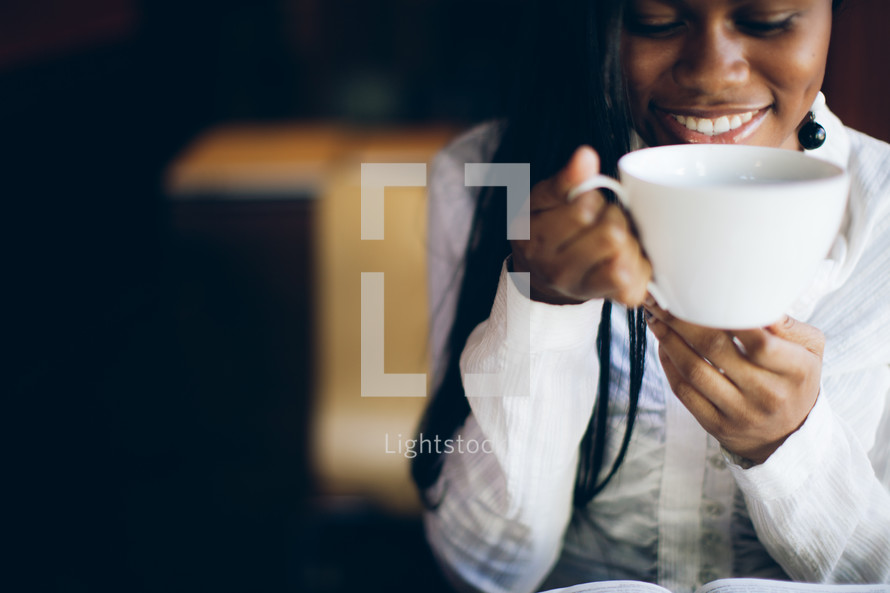 woman holding a coffee mug to her mouth over a Bible