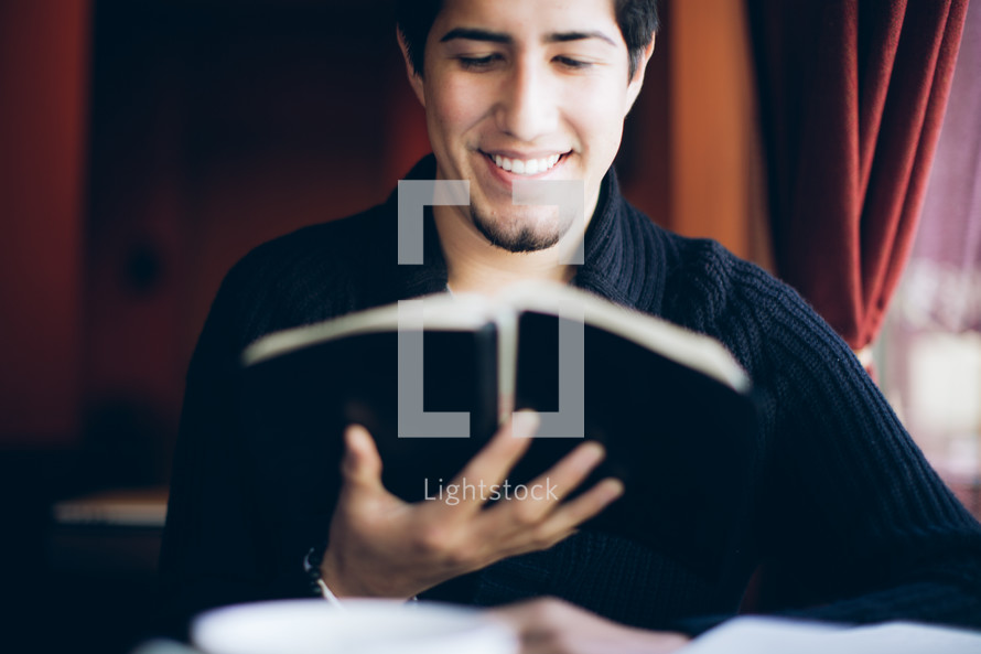 man reading a Bible and smiling at the Good News