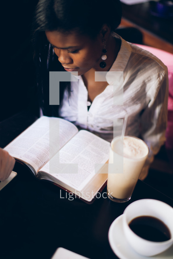 woman reading from a Bible at a Bible study at a coffee house