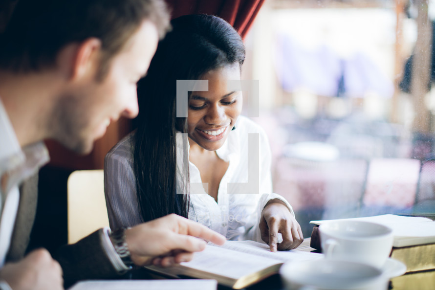 man and woman pointing to a Bible verse and smiling during a Bible study