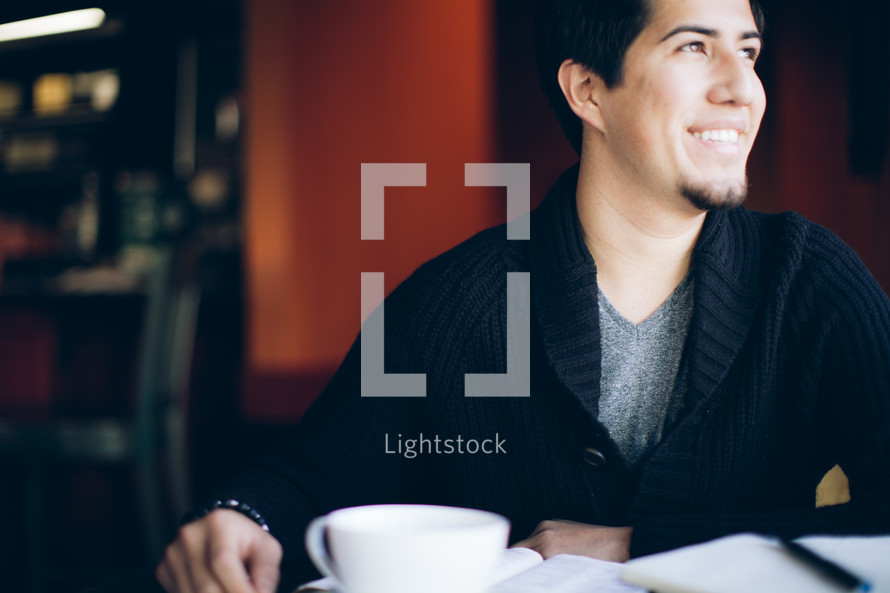 man with his head turned to the side sitting in front of a coffee mug and open Bible
