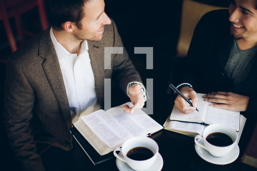 two men smiling and talking over coffee at a Bible study