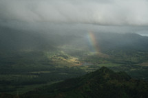rainbow peeking through the clouds over a green landscape