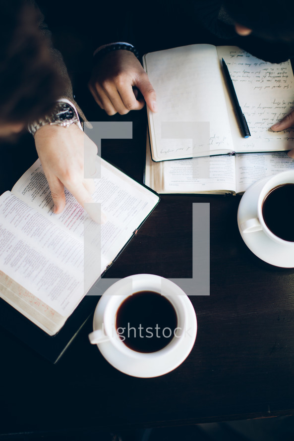 fingers pointing to a Bible verse