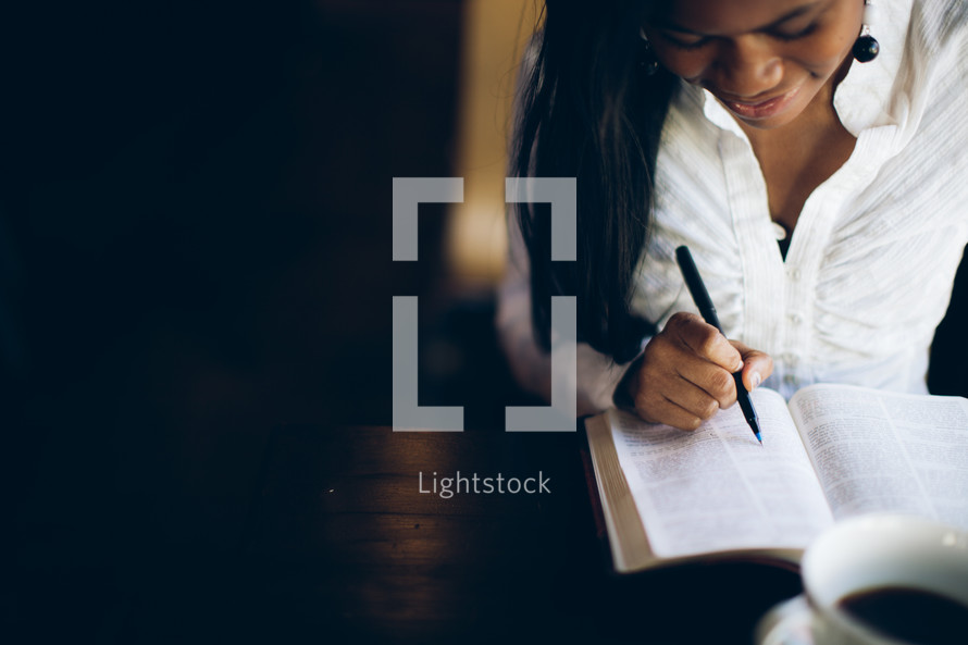 woman underlining a Bible verse in a Bible